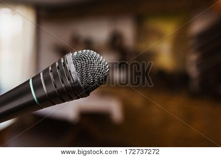 A microphone on a dark background. Evening in the restaurant. Conduct performance. Microphone close-up