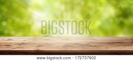 Sunny spring background with out of focus trees and an empty rustic wooden table for a concept