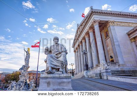 Roman statue at historic building of the Austrian parliament in Vienna, on ringstrasse street, Austria, sunny day and blue sky