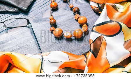Autumn set of womens accessories. Silky necktie, leather gloves, eye wear and beads