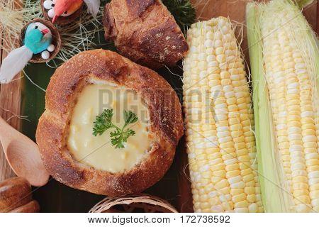 Corn soup in bread bowl with fresh corn