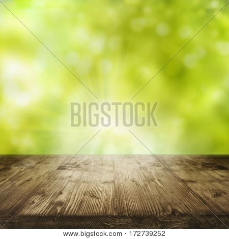 Fresh green spring background in front of an old rustic wooden table for a concept