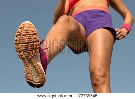 Young woman runner running,training for marathon run.View from below