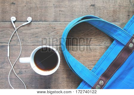 Flat lay of cup of coffee earphone and blue hand bag Summer concept