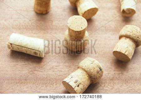 Seven caps of cork champagne randomly scattered on a wooden board.
