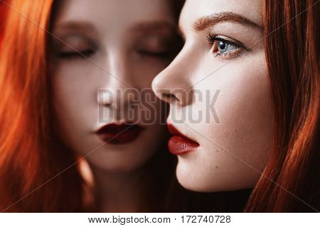 Beauty portrait of two redhead woman on the black and red background. Two lesbian women. Long red hair. Love between redhead girls. Portrait of a woman in profile