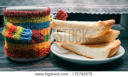 Mug in colorful sweater and pieces of cheese cake