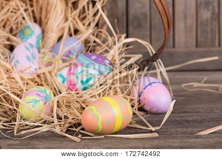 Colorful Easter eggs spilled from a basket on a wooden surface