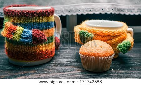 Big mug and small cup in colorful sweaters and muffin