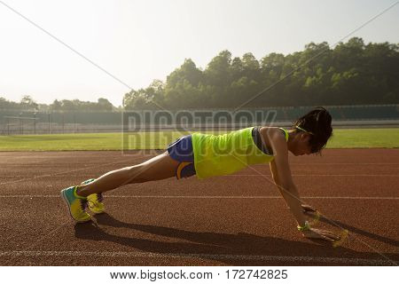young fitness woman runner push up before run