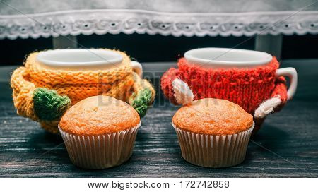 Two cups in colorful sweaters and small muffins