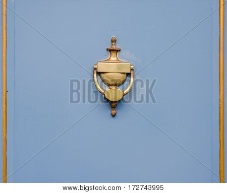 original brass knocker in the shape of an antique vase on the blue door with golden frames stylized object on the door