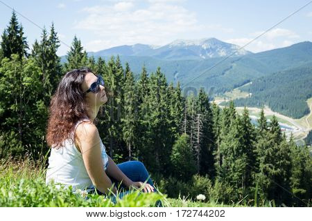 Beautiful woman sits on meadow in the mountains. The mountains and woodland in the background. Bukovel. Ukrainian Carpathians.