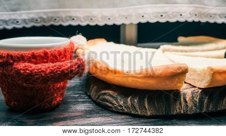 Cup in red sweater and pieces of cheese cake