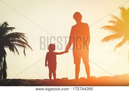silhouette of father and little daughter walk at sunset tropical beach