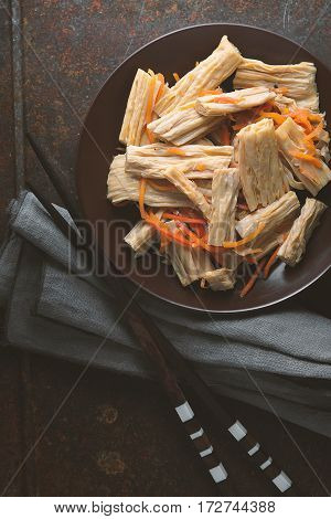 Asparagus in Korean and carrots in a ceramic dish on a napkin vertical