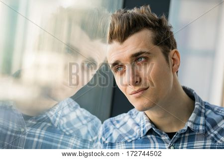 Young Man In Checkeret Shirt Standing Next To Window