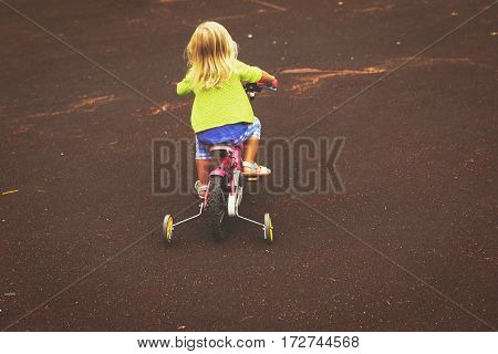 little girl learning to ride bike outdoors