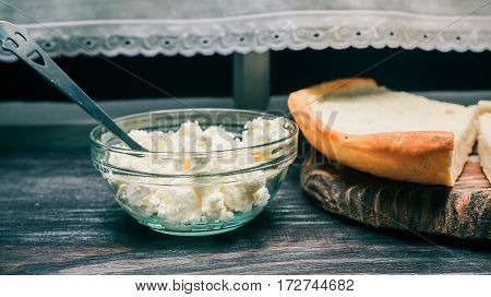 Farmer cheese with smiling teaspoon in bowl and homemade cheesecake