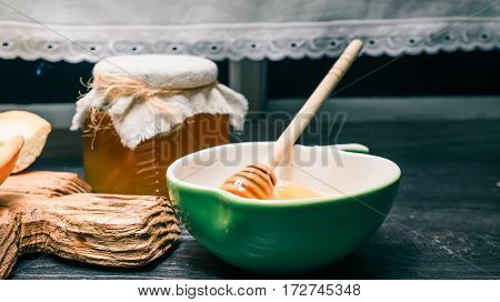 Honey in glass can and bowl with dipper. Edge of homemade cheesecake pieces on wooden serving board