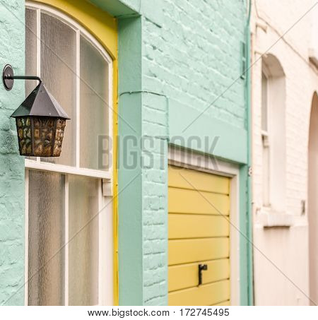 original lamp on the facade of the building artistic lamps in the background painted brick facades of buildings interesting colors Click connection bright green and beige with elements of yellow decoration