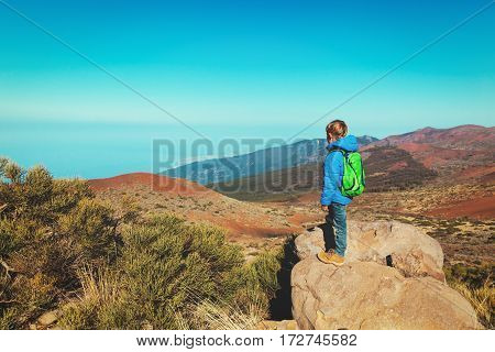 little boy hiking in mountains looking at beautiful landscape