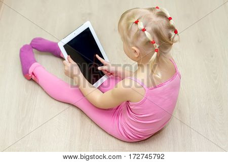 Little Girl In A Pink Dress Presses A Tablet Screen