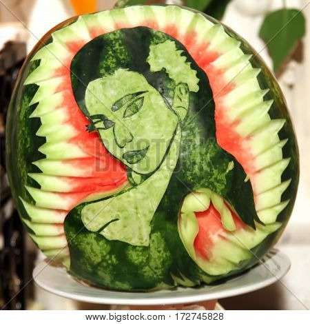 Carving sculpture of the girl's face from a freshly cut watermelon
