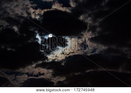 The night is dark gloomy sky. The moon shines through the clouds. Full moon.  Night gothic background.