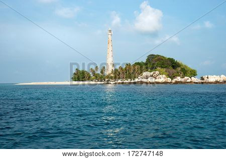White lighthouse standing on an island in Belitung at daytime with no people around.
