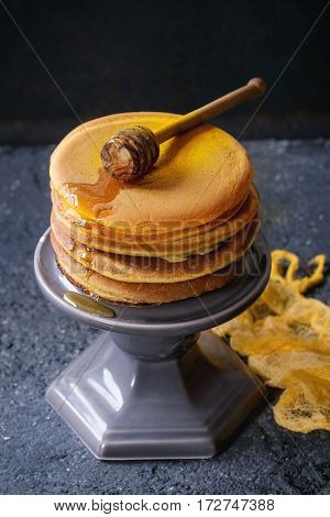 Stack of homemade american ombre yellow turmeric pancakes with honey sauce served on cake stand with wooden dipper over black stone texture background. High angle view