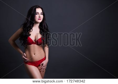 Sexy Beautiful Plus Size Model In Red Lace Lingerie Over Black Background With Copy Space