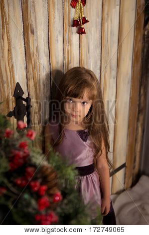 Girl stand on the porch waiting for Santa Claus. The concept of magic in Christmas.