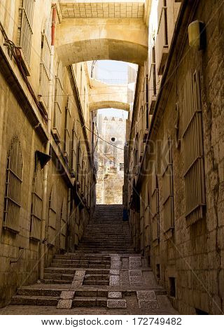 En empty street of the old city in Jerusalem Israel. Stone walls with barred windows stairs leading up