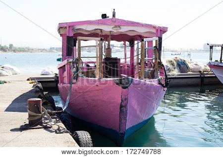 An old pleasure boat pink color waiting for tourists on a mooring in Acre Israel.