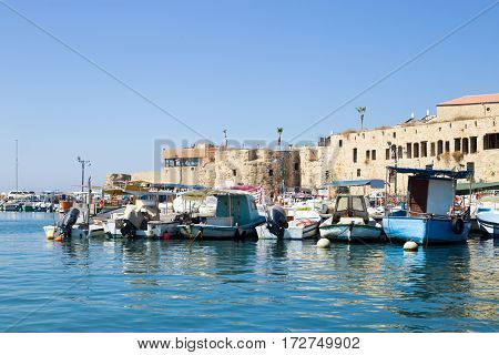 Old boats on the quay in Acre Israel. Brick wall in the background and nobody around