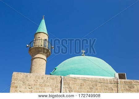 A beautiful Sinan Basha Mosque with green dome in the old town of Acre Israel. Muslim mosque and minaret