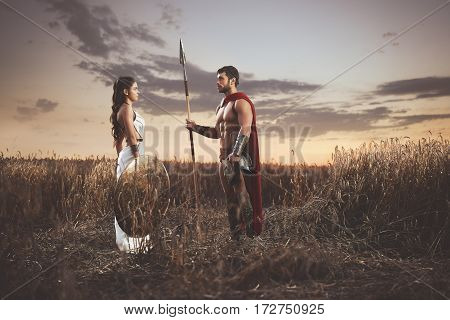 Beautiful brunette woman wearing in dress like greece style holding iron shield and husband warrior wearing like spartan. Couple meeting after war among grass in field, looking each other.
