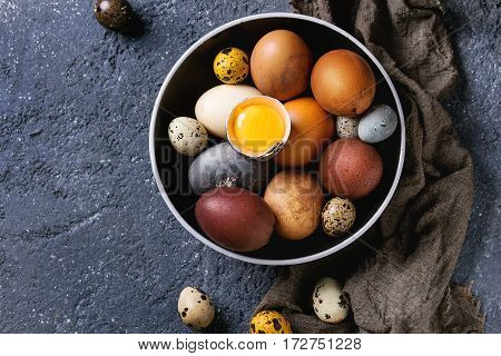 Brown and gray colored chicken and quail Easter eggs in black ceramic bowl with yolk, sackcloth rag over black concrete texture background. Top view, copy space