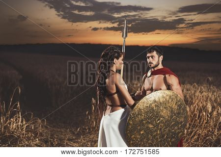 Portrait of couple meeting after war in field. Beautiful woman with long hair wearing like greece in white dress looking face to face with man warrior wearing like spartan.