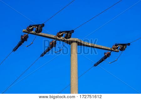 Industrial power line pylon close up in front of a clear blue sky