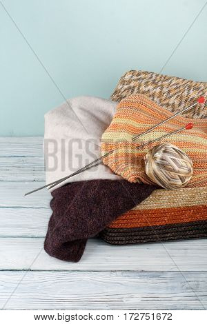 Ball of wool needles and woolen sweater with spokes for handmade knitting in basket on wooden table