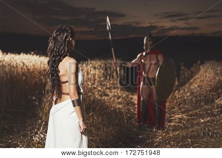Back view of incognito of woman in white dress looking to unrecognizable man in helmet and armour and weapon. Couple meeting and bid farewell before war at field.