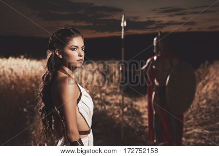 Woman wearing in white dress looking away over shoulder against unrecognizable man in helmet, armour and weapon. Couple meeting after war in field at night time.