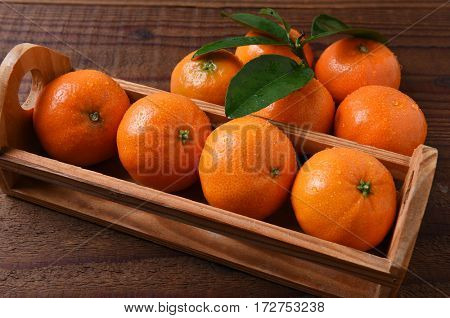 Closeup of a small crate of Mandarin Oranges on a rustic wood table.