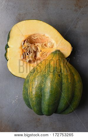 High angle view of an Acorn Squash cut in half on a metal baking sheet.