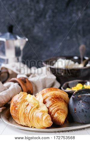 Breakfast with two croissant, butter, cup of coffee, cottage cheese and sliced mango fruit, served on serving metal tray with textile napkin on white and gray concrete texture background. Close up.