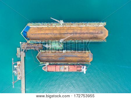container ship in import export and business logistic.By crane Trade Port Shipping.Tugboat assisting cargo to harbor.Aerial view.
