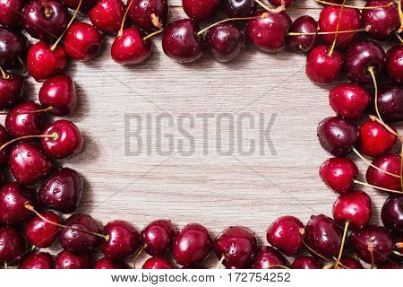 Ripe red cherries lie on a wooden background. Frame of ripe summer berries. Space for text copyspace from  red cherries