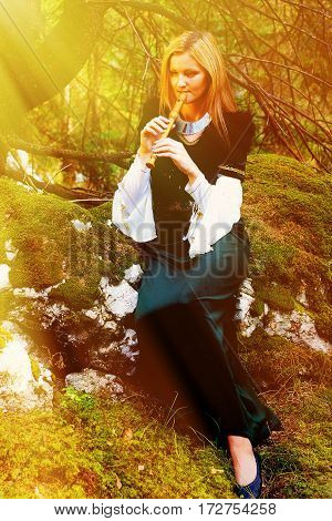beautiful girl in a historical costume playing her flute in forest. Light effect